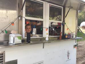 Boy looking out window from inside the sausage cart