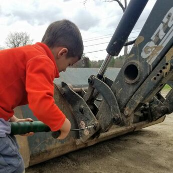 child repairing tractor